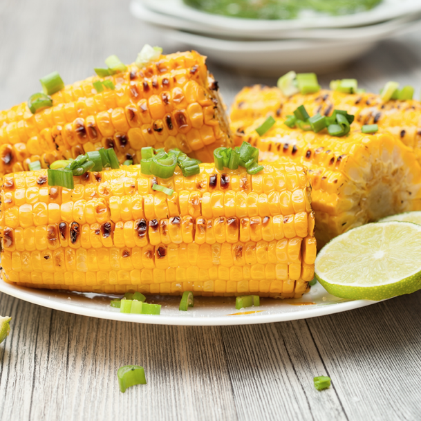 grilled seasoned corn on plate with lime
