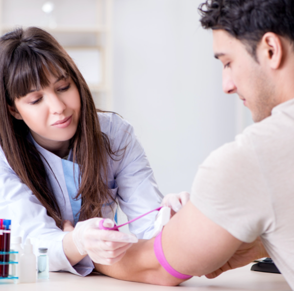 phlebotomist drawing blood from man