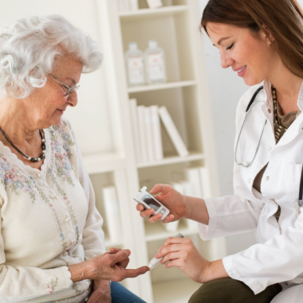 phlebotomist using finger prick test on older woman