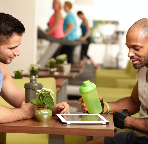 two men talking at gym with green smoothies