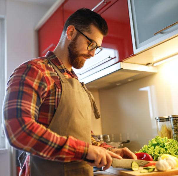 athletic man cutting vegetables